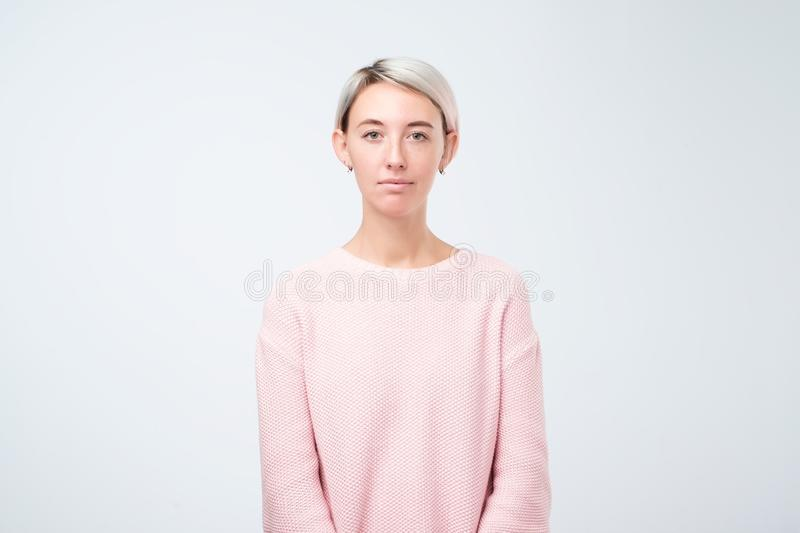 Portrait of stylish young pretty woman smiling standing in pink sweater on white studio background stock image