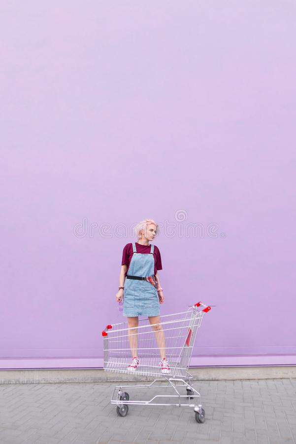 Portrait of a stylish young woman with pink hair standing in a cart on the background of a purple wall royalty free stock images