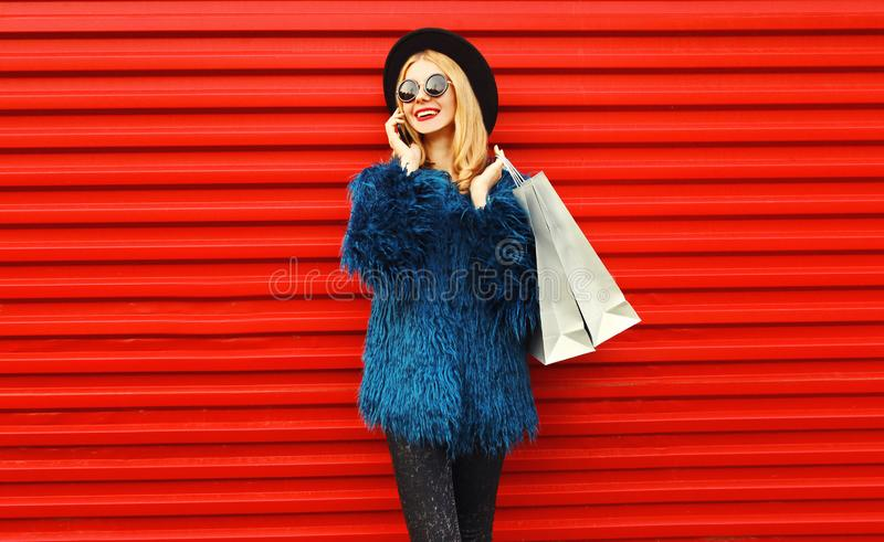Portrait stylish young woman with shopping bags calling on phone wearing blue faux fur coat, black round hat royalty free stock photography