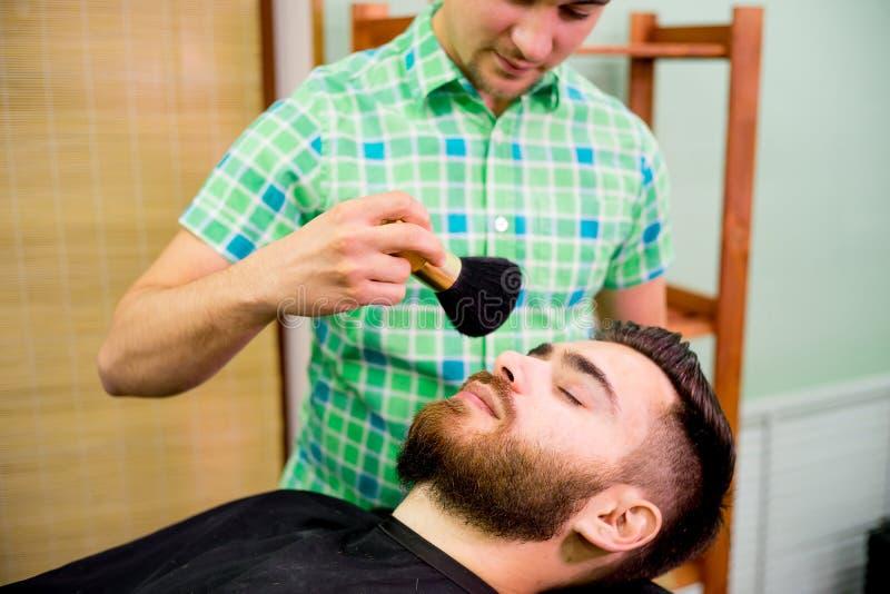 Stylist trimming beard stock image