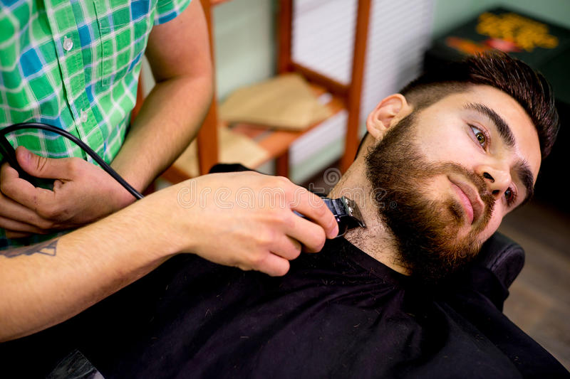 Stylist trimming beard royalty free stock photography