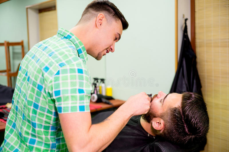 Stylist trimming beard royalty free stock images