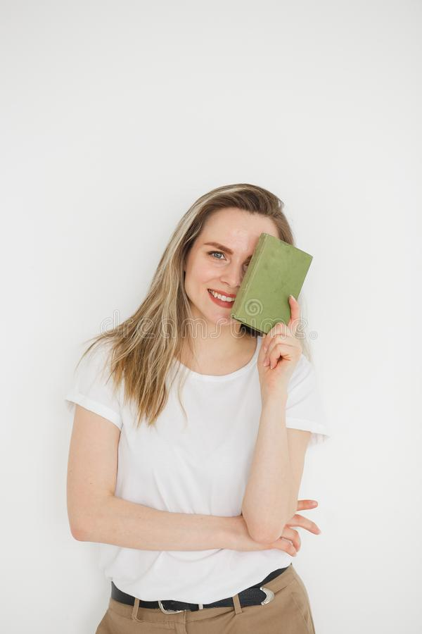 Portrait of succesful smiling woman in casual wear with green book on light background stock photo