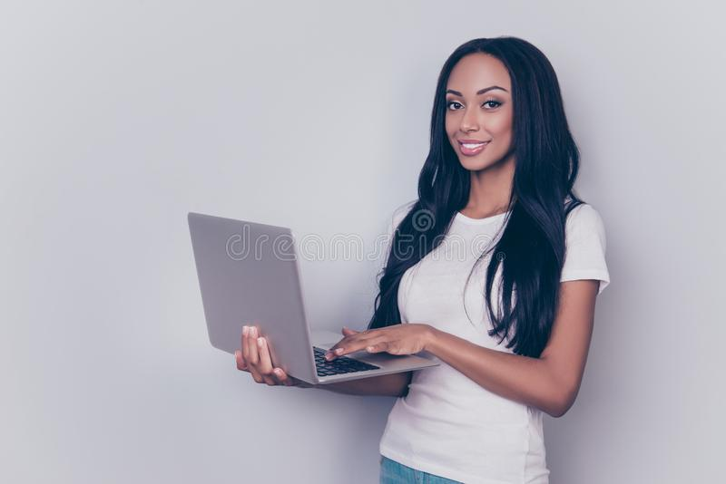 Portrait of successful afro lady with laptop, typing on a keyboard, standing on pure gray backgrund, looking in the camera, She i royalty free stock photos