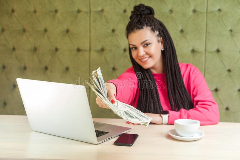 Portrait of successful attractive young woman with black dreadlocks in pink blouse is sitting, holding many dollars, giving you stock images