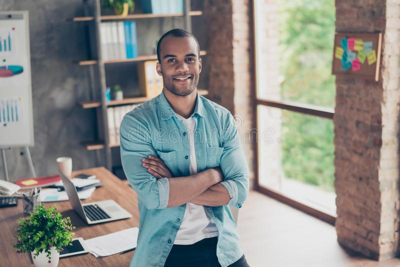 Portrait of successful black guy, looking at the camera, standing with crossed arms at his work place in the office, in casual sma. Rt, smiling royalty free stock photo