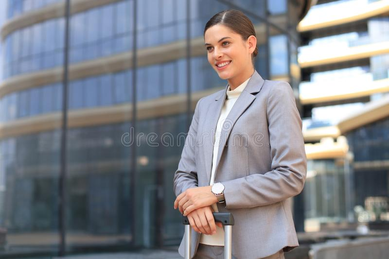 Portrait of successful business woman traveling with case at airport. Beautiful stylish female travel with luggage stock photo