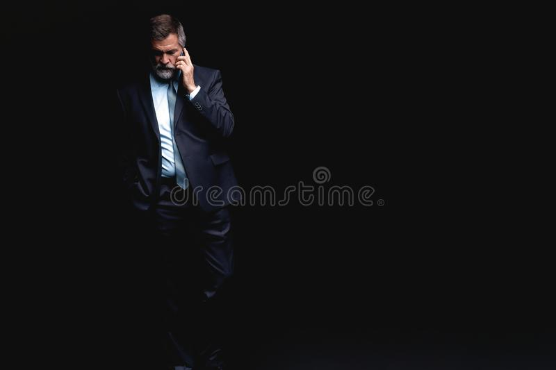 Portrait of a successful businessman on phone against black background. Portrait of a successful businessman on phone against black background stock image