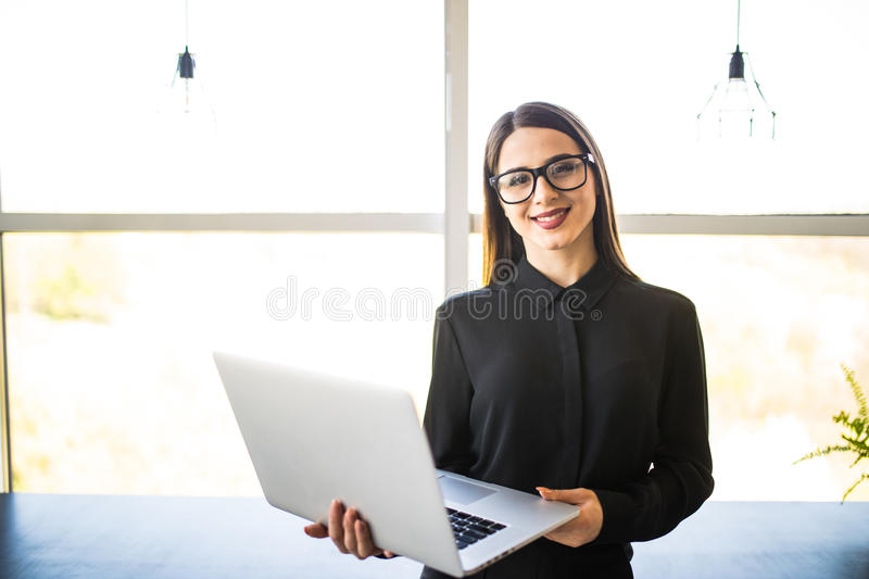 Portrait of successful businesswoman holding laptop in her hands. Happy beautiful confident woman standing at office with notebook. Business People royalty free stock photo