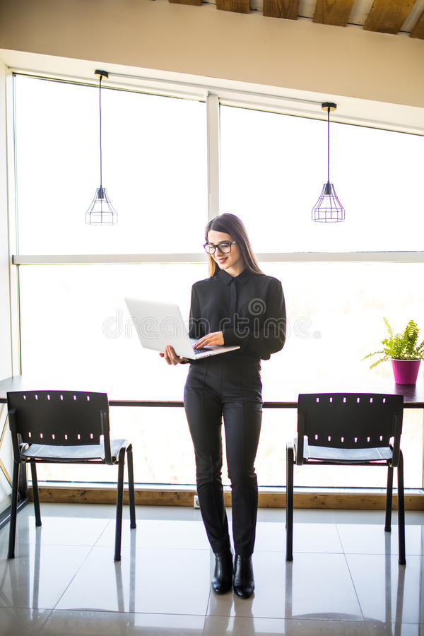 Portrait of successful businesswoman holding laptop in her hands. Happy beautiful confident woman standing at office with notebook. Business People stock image