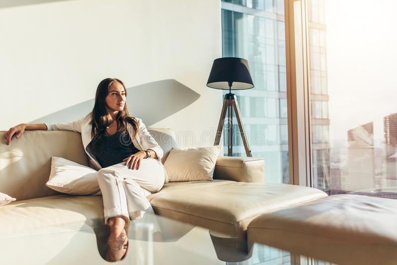Portrait of successful businesswoman wearing elegant formal suit sitting on leather sofa relaxing after work at home stock photography