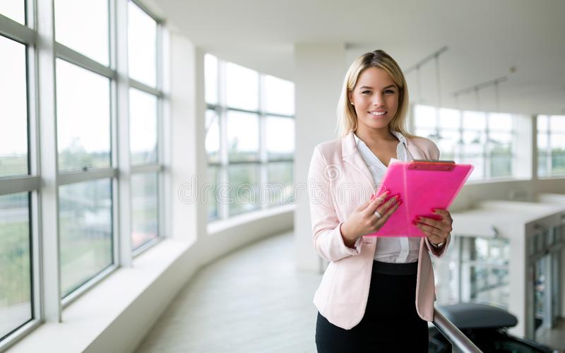 Portrait of successful cheerful businesswoman with paper documents working stock images