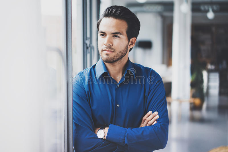 Portrait of successful confident hispanic businessman standing close from the window in modern office.Horizontal,blurred stock images