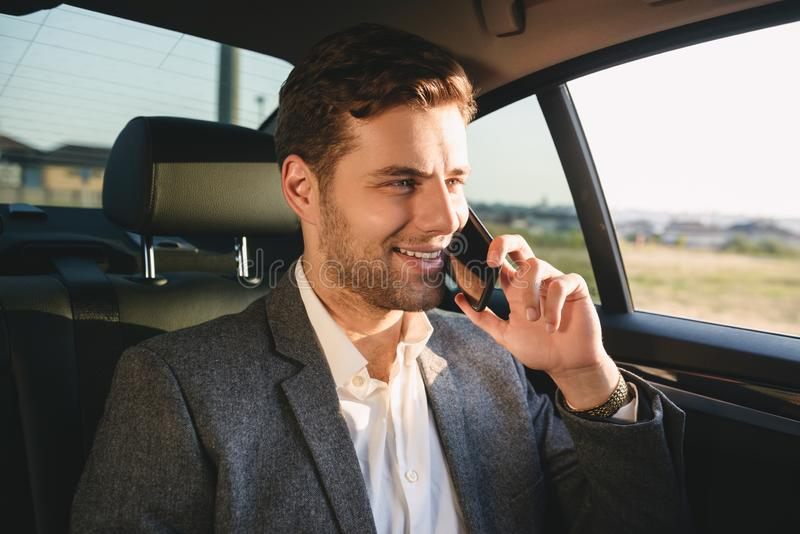 Portrait of successful director man in suit talking on smartphone, while back sitting in business class car. Portrait of successful director man in suit talking stock photo