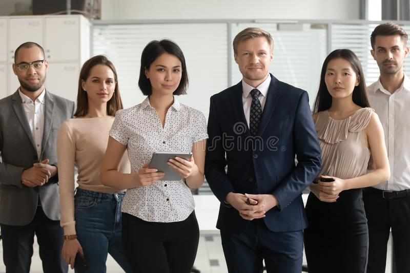 Portrait of successful diverse employees team standing in office stock photos