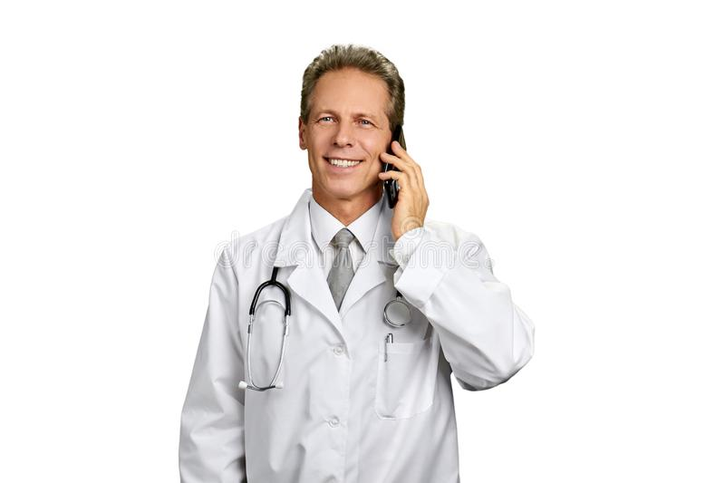 Portrait of successful doctor talking on phone. Smiling medical doctor with stethoscope talking on his cell phone, isolated on white background. Concept of royalty free stock photo