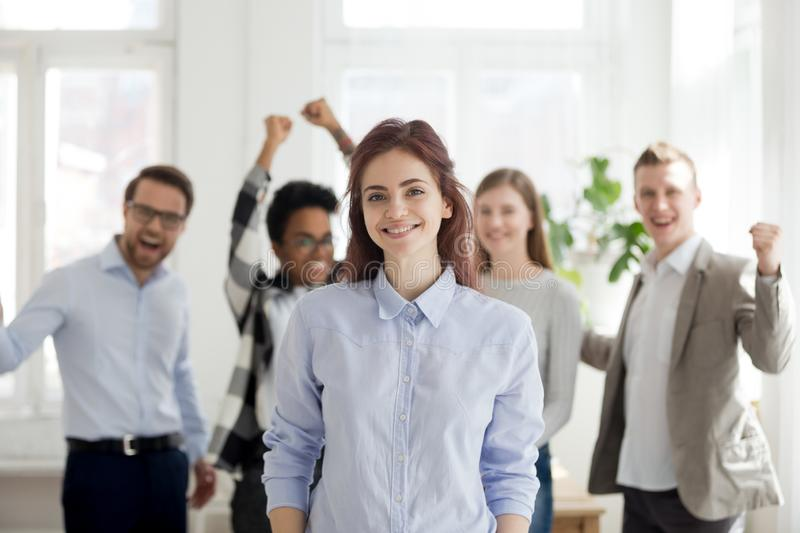 Portrait of successful female employee with excited colleagues a. Portrait of smiling female employee standing foreground, excited team or colleagues cheering at royalty free stock photo