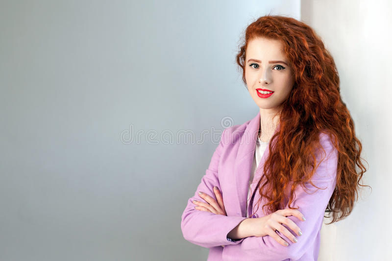 Portrait of successful happy beautiful business woman with red - brown hair and makeup in pink suit. royalty free stock images