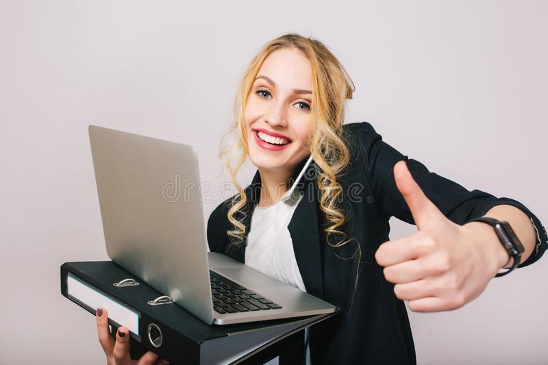 Portrait successful joyful businesswoman smiling to camera, holding laptop, folder, talking on phone isolated on white stock photo