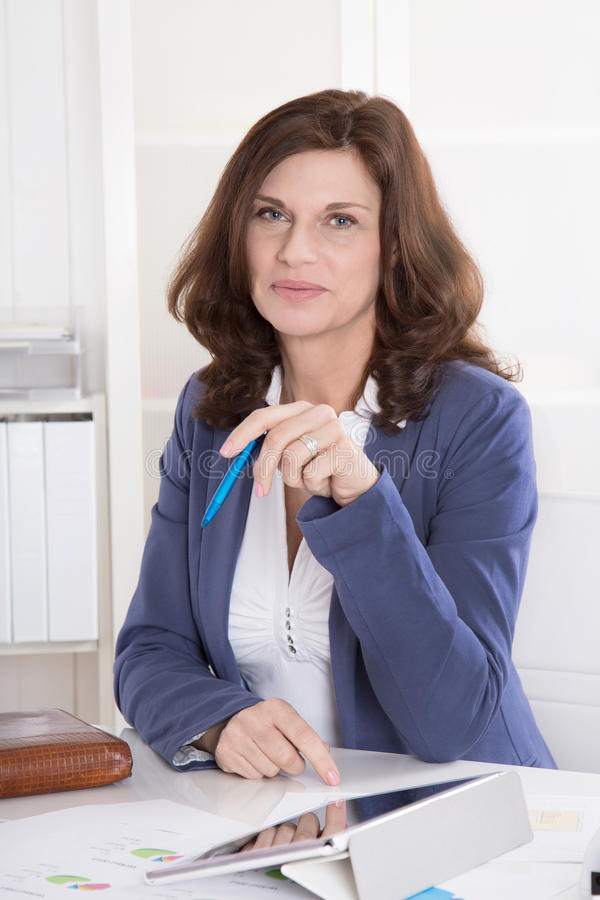 Portrait: Successful middle-aged attractive woman sitting in the royalty free stock images