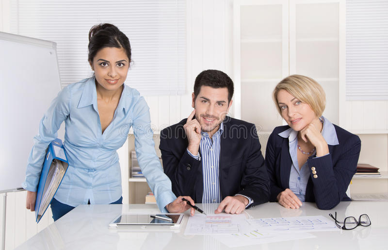 Portrait: successful smiling business team of three people; man. Portrait: successful smiling business team of three people; men and women in the office wearing stock image