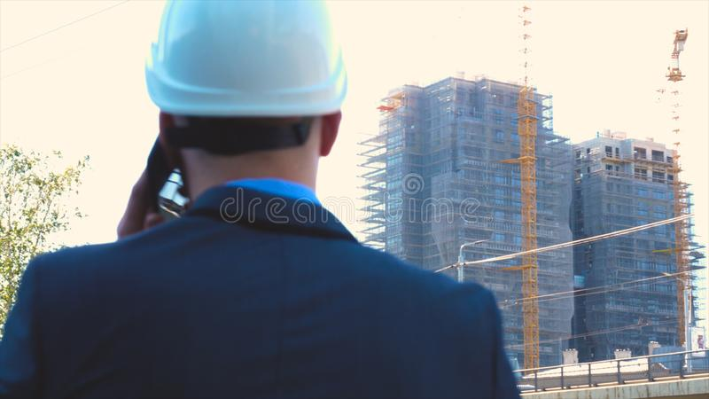 Portrait of a successful young handsome engineer, architect, builder, businessman, wearing a white helmet, in a suit, holding a pr stock image