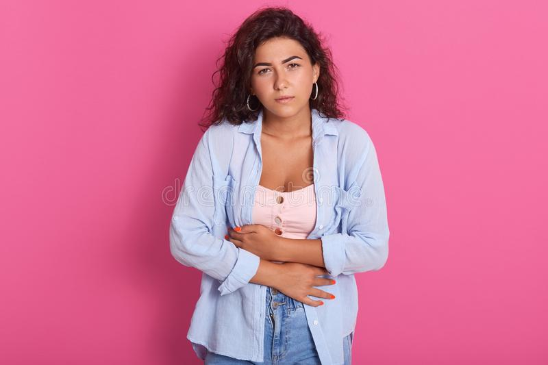 Portrait of suffering tired young woman keeping hands at stomach, having stomachache, feeling uncomfortable, being unhealthy, stock photo