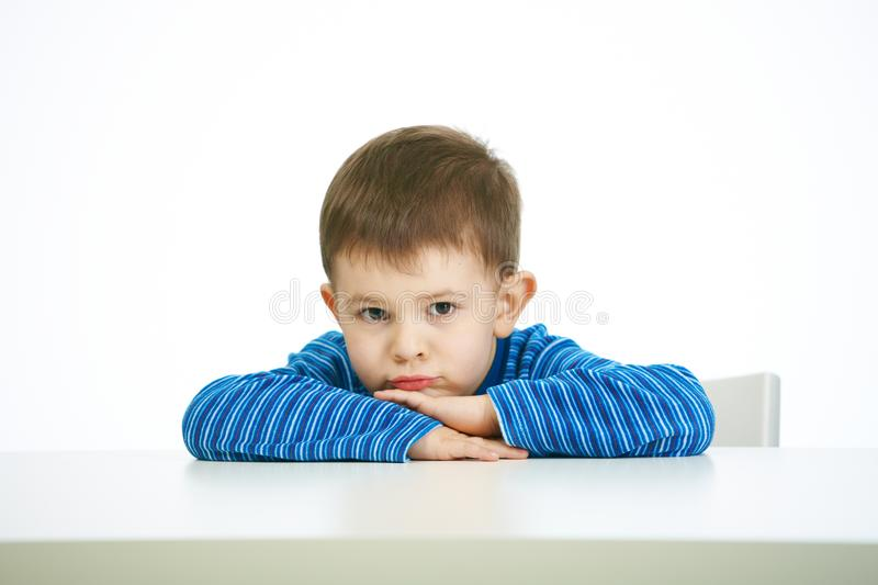 Portrait of sullen little boy sitting at table. Looking at camera, serious royalty free stock photo