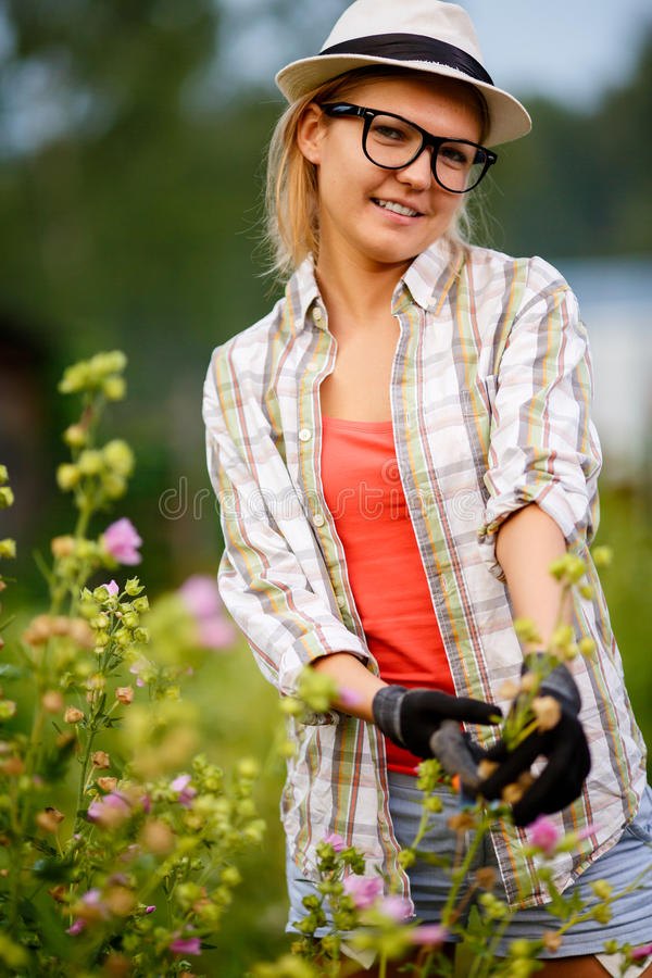Portrait in summer garden of young pretty woman gardening royalty free stock photo
