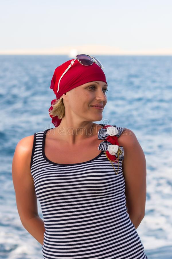 Portrait of a suntanned slender girl in a red bandana against the blue sea royalty free stock photo