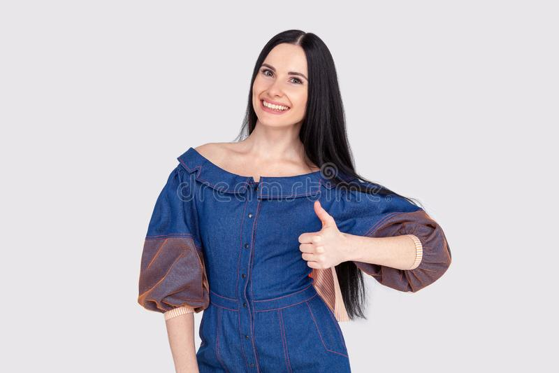 Portrait of supportive pleased and delighted female customer in jeans dress sharing positive feedback showing thumbs up gesture royalty free stock photos