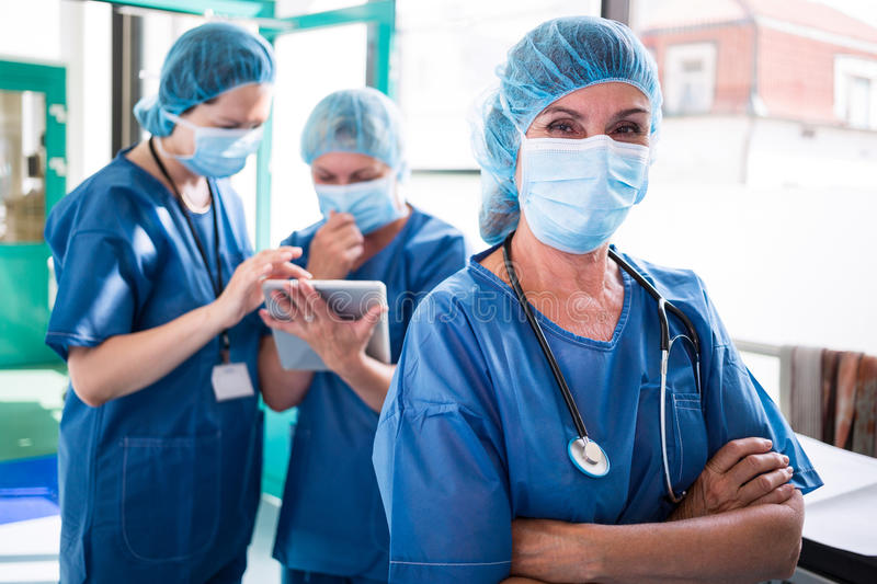 Portrait of surgeon standing with arms crossed while staff discussing over digital tablet in backgro stock images