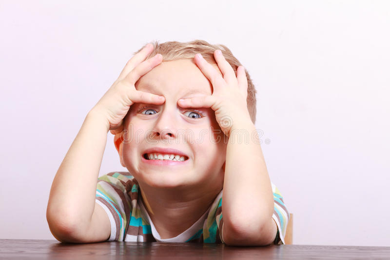 Portrait of surprised angry emotional blond boy child kid at the table. Portrait of surprised angry emotional blond boy. Child kid making silly funny face at the royalty free stock photography
