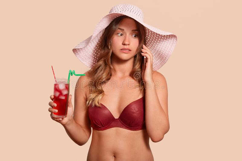 Portrait of surprised attentive lady wearing red swimming suit and hat, standing isolated over beige background, holding red cold royalty free stock images