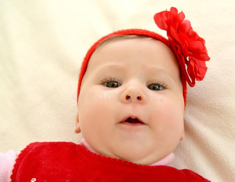 Portrait of the surprised baby with a red flower on the head stock photo