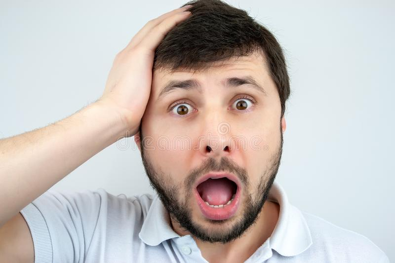 Portrait of a surprised bearded man with eyes and mouth wide open, holding his head with his hand stock photo