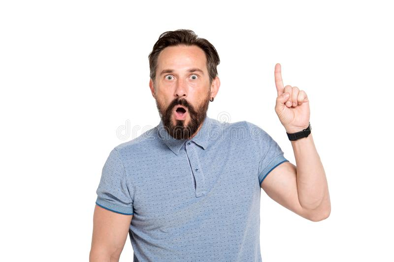 Portrait of surprised bearded man raising his forefinger. Bright idea. Mature bearded man expressing surprise while keeping his mouth opened and raising his stock image