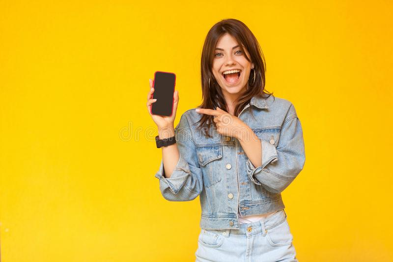 Portrait of surprised beautiful brunette young woman in denim casual style standing, looking at camera with amazed face and stock photography
