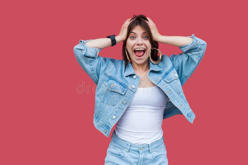 Portrait of surprised beautiful brunette young woman with makeup in denim casual style standing, holding her head, looking at royalty free stock images