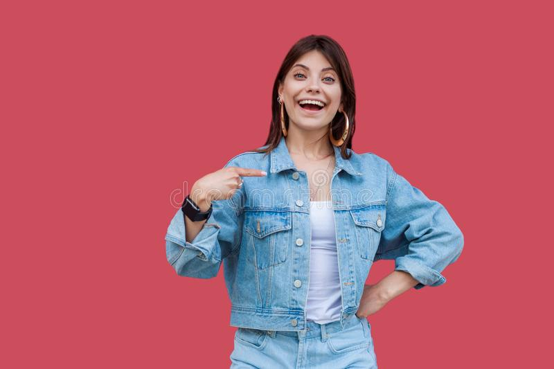 Portrait of surprised beautiful brunette young woman with makeup in denim casual style standing, pointing herself and looking at royalty free stock photography