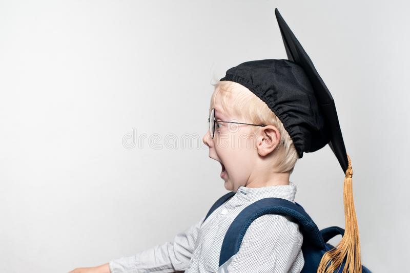 Portrait of a surprised blond boy in glasses, an academic hat and a schoolbag on a white background. School concept royalty free stock photography