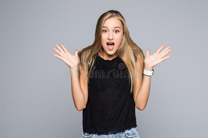 Portrait of Surprised brunette woman in black t-shirt looking at the camera over gray background royalty free stock photo
