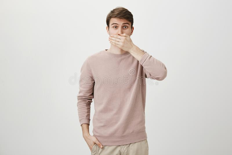 Portrait of surprised caucasian male lifting eyebrows and looking with widened eyes at camera while covering mouth with. Hand, standing against gray background stock photography