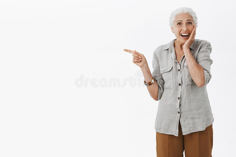 Portrait of surprised and delighted amazed cute granny in casual shirt touching cheek gently from excitement smiling royalty free stock photography