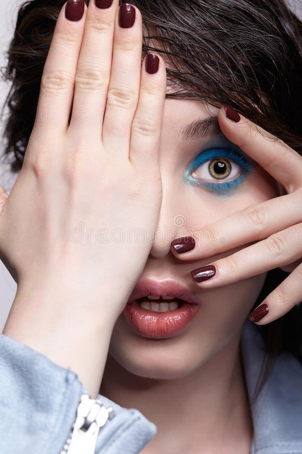 Portrait of surprised female in blue jacket with hand on face. Woman with unusual beauty makeup and wet hair, and blue shadows royalty free stock photo