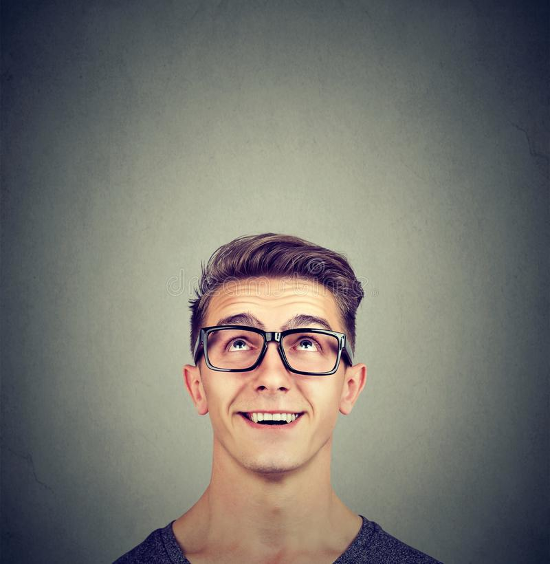 Surprised happy young man wearing glasses looking up stock photos