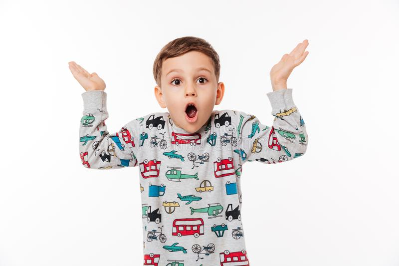 Portrait of a surprised little kid standing and shrugging shoulders. Isolated over white background royalty free stock photo