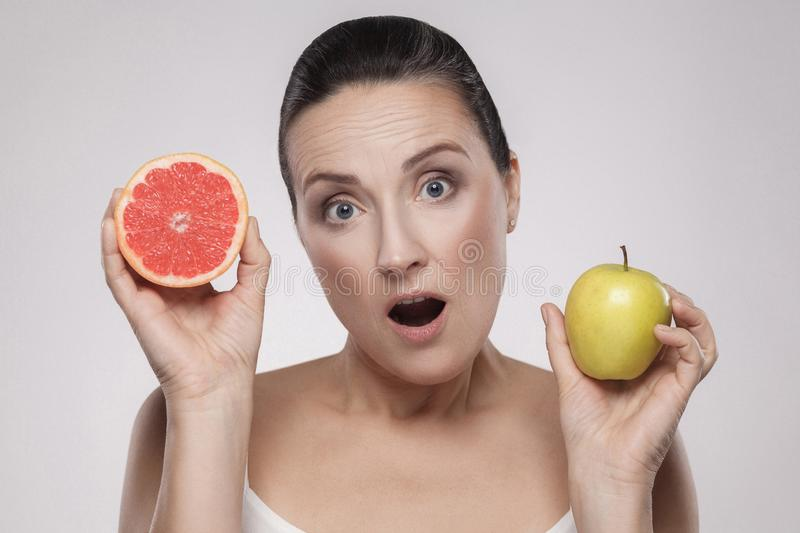 Portrait of surprised middle aged woman with perfect face skin holding fresh slice grapefruit and apple in her hands and open stock photos