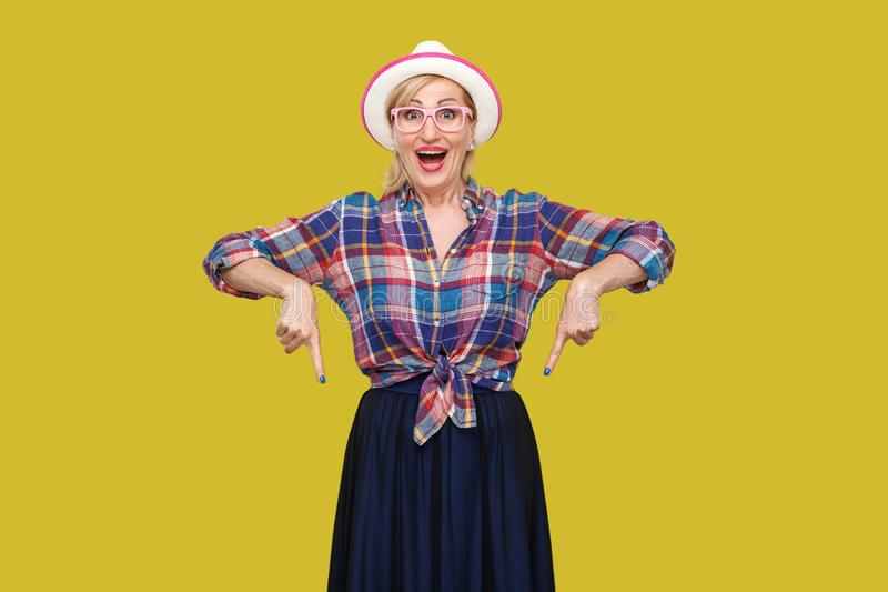 Portrait of surprised modern stylish mature woman in casual style with hat and eyeglasses standing, amazed looking at camera and. Pointing down. indoor studio stock images