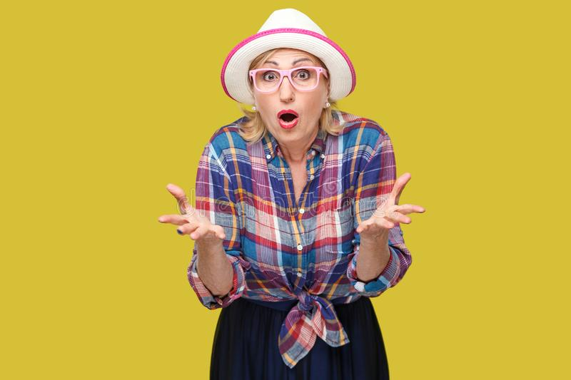 Portrait of surprised modern stylish mature woman in casual style with hat and eyeglasses standing, raised arms, looking at camera. With shocked face. indoor royalty free stock image